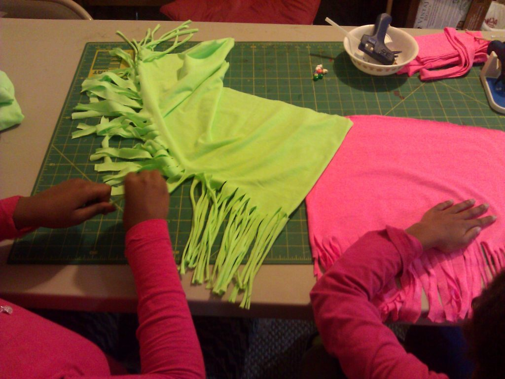 two girls working on making t-shirt scarves
